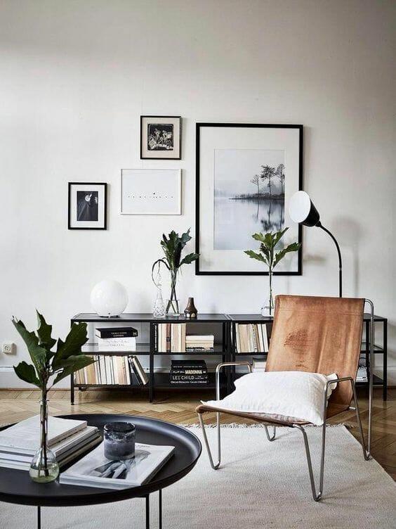 salon w stylu skandynawskim nowoczesny welurowy fotel, czarna komoda i zdjęcia w ramkach