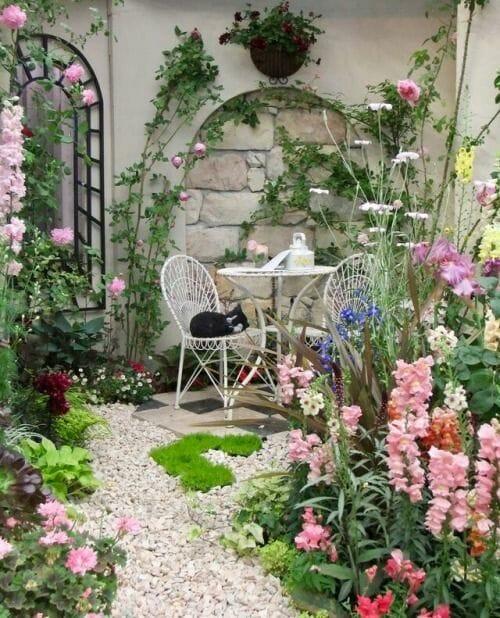 Aranżacje ogrodów kwiaty stoliczek metalowe krzesła