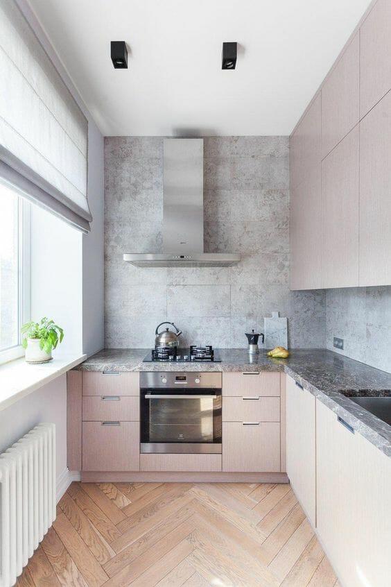 parkiet drewniany w kuchni z jasno różowymi szafkami z marmurowym blatem