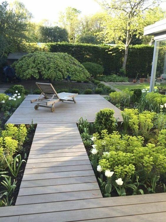 drewniany podest w ogrodzie kwiaty i krzewy