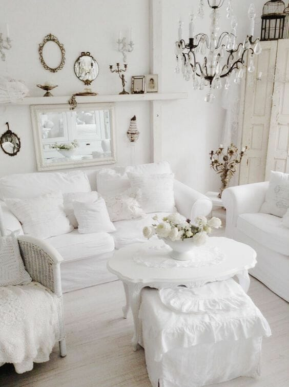 biały salon shabby chic poduszki z falbanami mosiężne dodatki kryształowy żyrandol