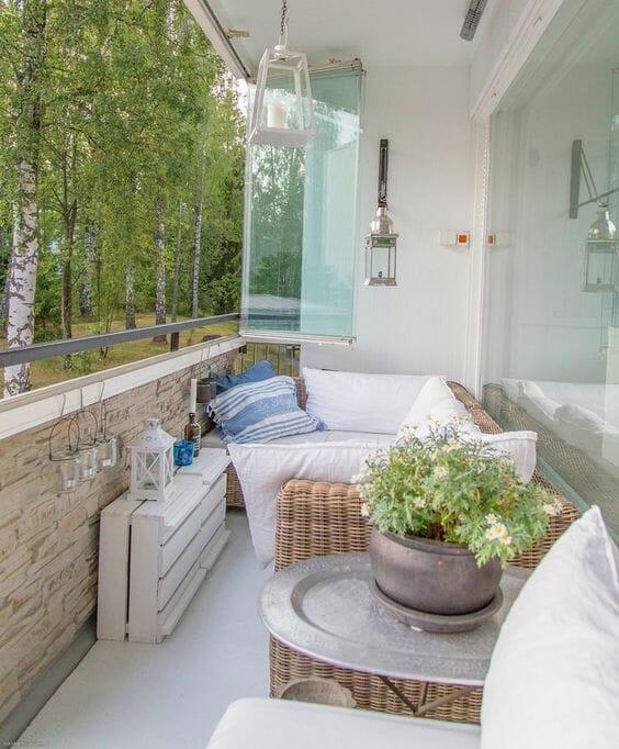 biało beżowy balkon z wiklinowymi meblami i białymi tekstyliami