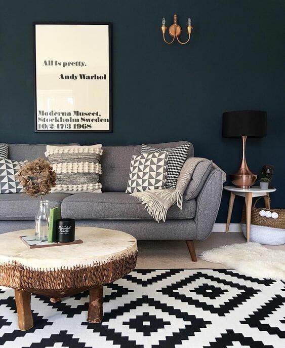 aztecki dywan czarno-bialy sciany kolor butelkowa zielen, lampa, sofa stolik z drewna