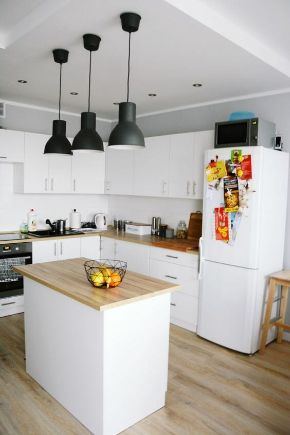 biała kuchnia z drewnianym blatem czarne zwisające lampy w stylu skandynawskim