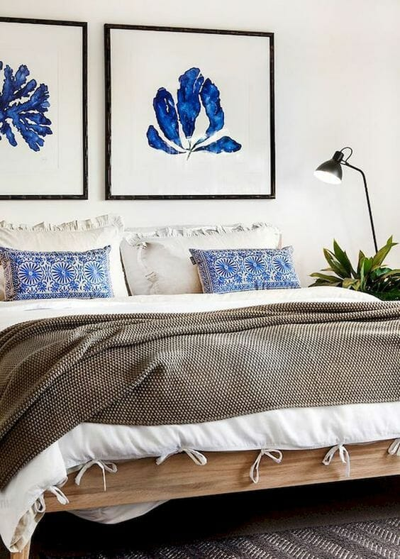 jasna sypialnia z akwarelą obrazami kwiatów nad łóżkiem i białą pościelą