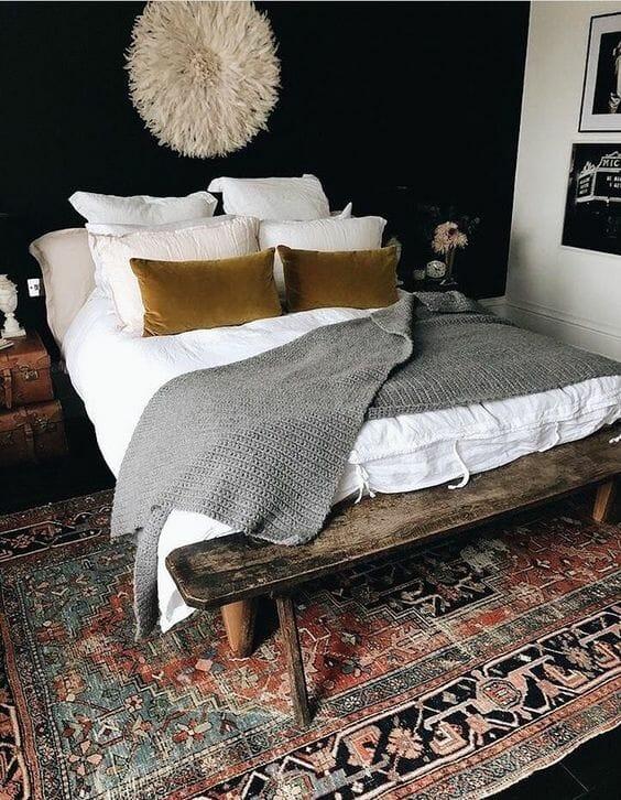 czarna sypialnia z rustykalnym dywanem i szarym pledem