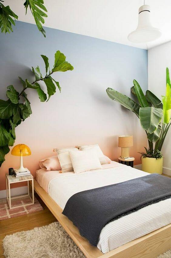 gradient na ścianie różowo-niebieski duże kwiaty do sypialni łóżko biała pościel lampa vintage