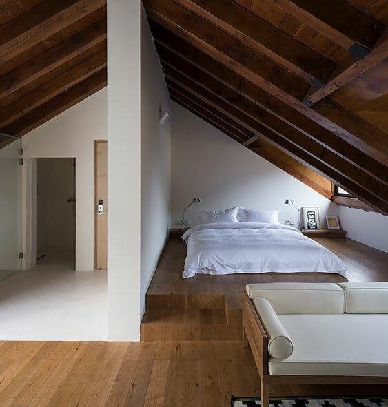 sypialnia na strychu białe ściany ukosy z drewna materac na podłodze