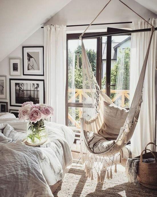 jasna sypialnia na poddaszu z plecioną huśtawką, świeżymi kwiatami i ramki ze zdjęciami inspiracje