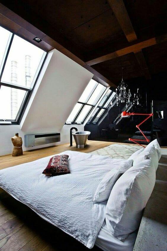adaptacja poddasza w postaci sypialni z czarnymi ścianami i dużymi oknami dachowymi, czerwony akcent kolorystyczny w postaci loftowej lampy