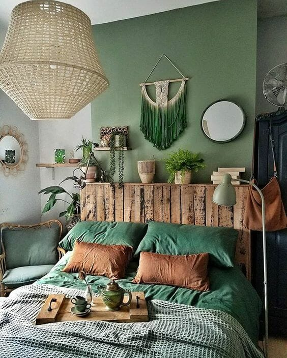 zielona sypialnia z drewnianymi dodatkami w postaci zagłówka, tacy, lampy i półki, wiklinowa lampa, lustro boho makrama wisząca nad zagłówiem