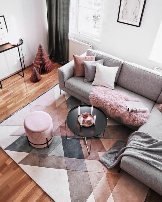biały salon z szarą kanapą i różowymi dodatkami