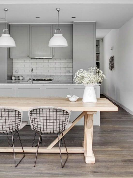 szara kuchnia z marmurowym blatem i białymi kafelkami i drewnianym stołem