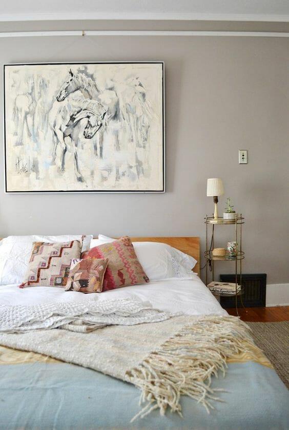 beżowe ściany w sypialni obraz wełniany pled lampka nocna poduszki aztec