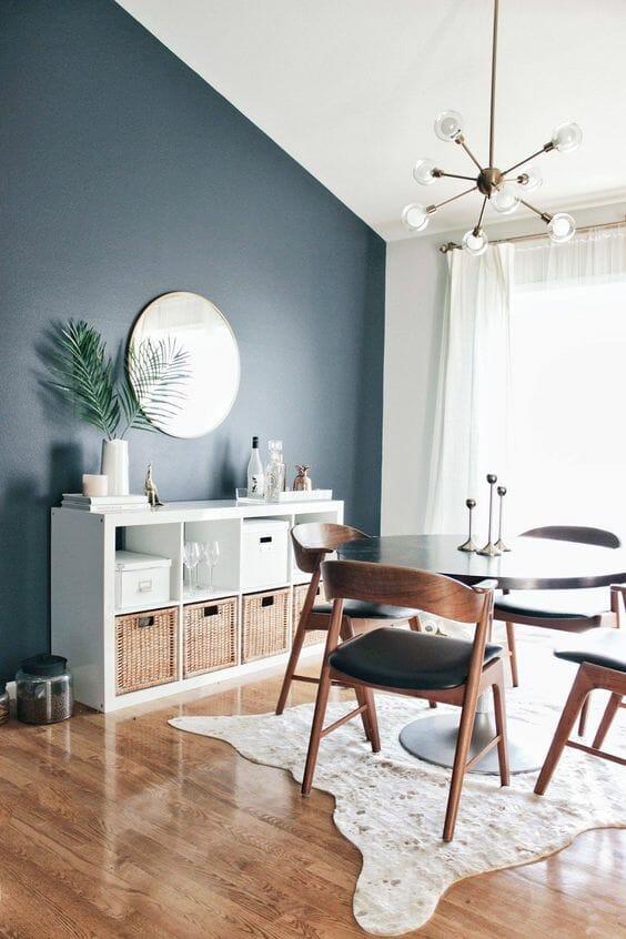 szaro granatowy salon z okragłym lustrem metalowym żyrandolem i drewnianymi krzesłami vintage