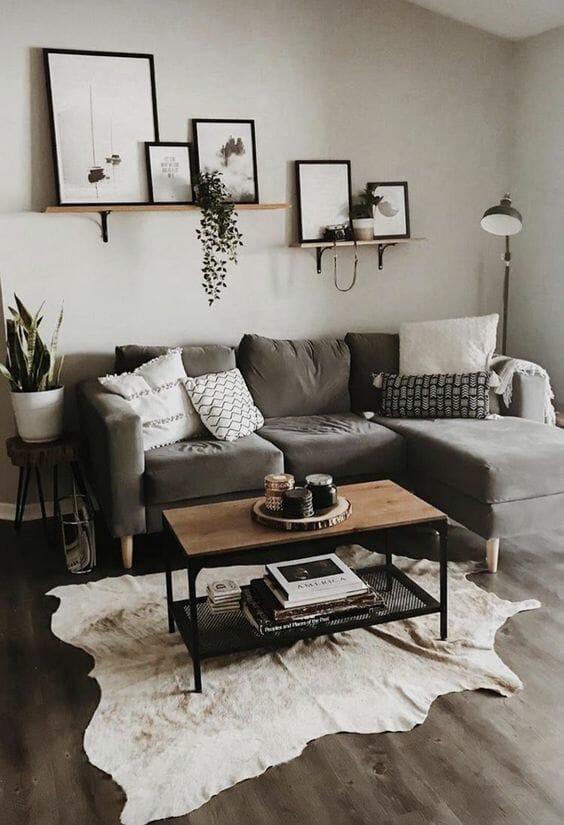 Szary kolor ścian w salonie z grafitową kanapą i dywanem ze skóry