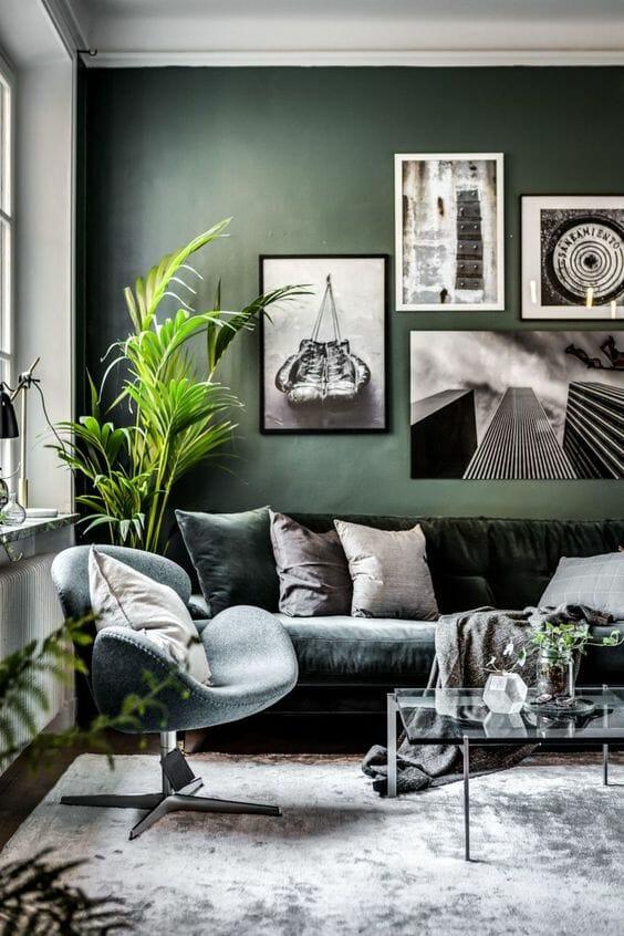 szaro zielony salon z welurową kanapą i szklanym stoliczkiem z czarno-białymi zdjęciami na ścianie