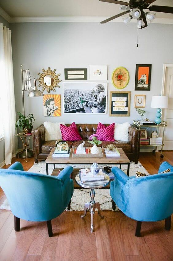 szary salon ze skórzaną kanapą i niebieskimi fotelami i różowymi poduszkami