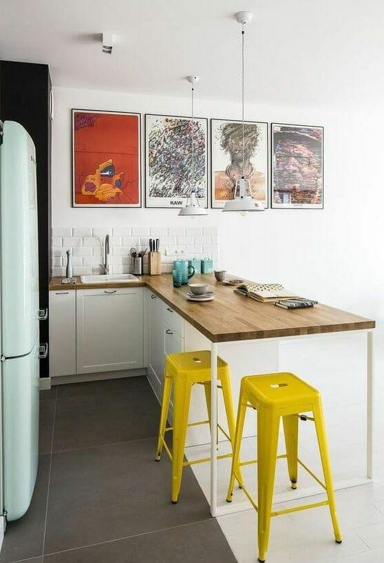 kuchnia nowoczesna biało czarno szara żółte stołki barowe grafiki w ramkach