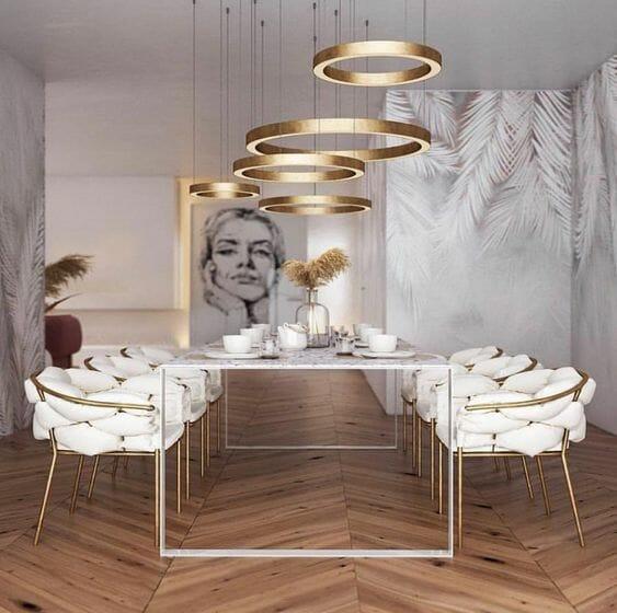 lampy do salonu w postaci złotych obręczy nad stołem jadalnianym