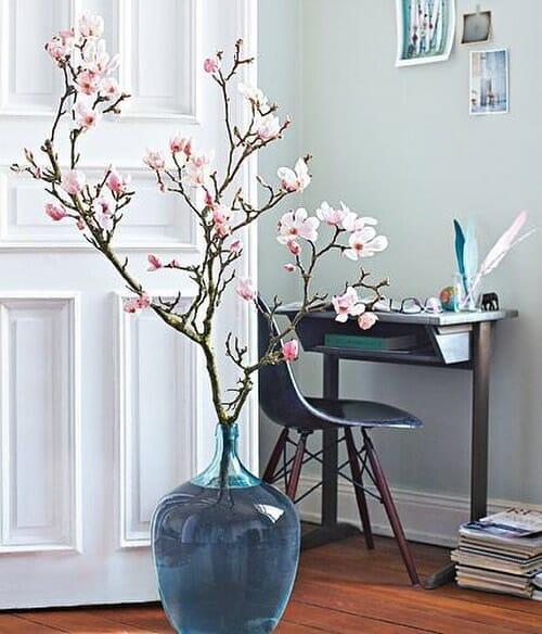 gałązki magnolii w dużym wazonie w kształcie gąsiora