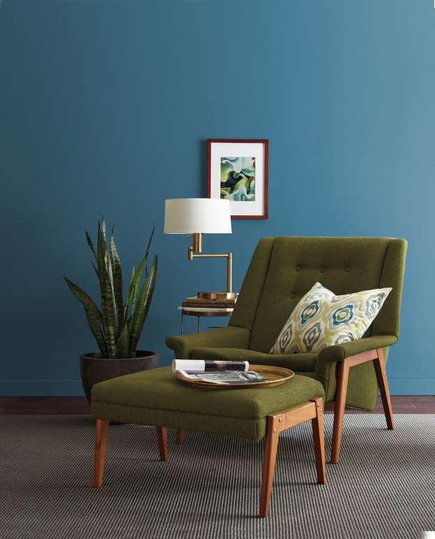 Modne kolory ścian do salonu, niebieskie ściany, zielony fotel, złote dodatki