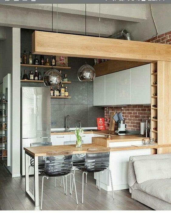 industrialna kuchnia z wyspą z drewnem i cegłą na ścianach