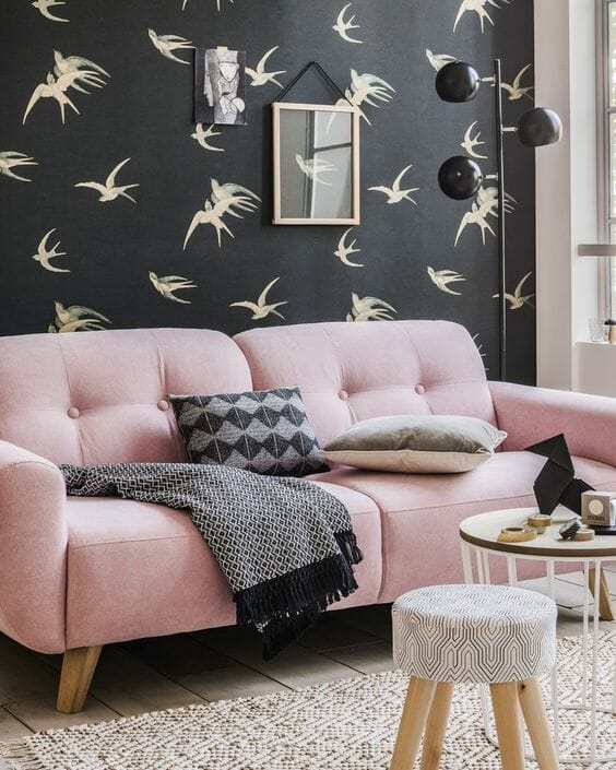 różowa kanapa na tle czarnej tapety