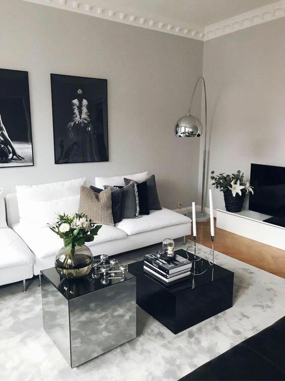 szary salon z lustrzanym stolikiem i czarnymi obrazami