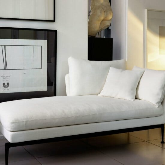 biały minimalistyczny szezlong z poduszkami leżanka